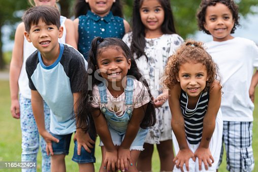 An adorable group of multi-ethnic kindergarten children pose for a portrait outside in  the grass. They are all smiling while huddled in close to each other. It is a sunny day with lots of natural light.