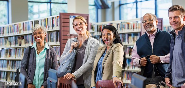 877026356 istock photo Multi-ethnic group of adults standing in library 1130543018
