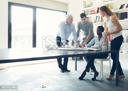 Multi-Ethnic Group of architects people on meeting in modern office discussing and drinking coffee. Having relaxed conversation.