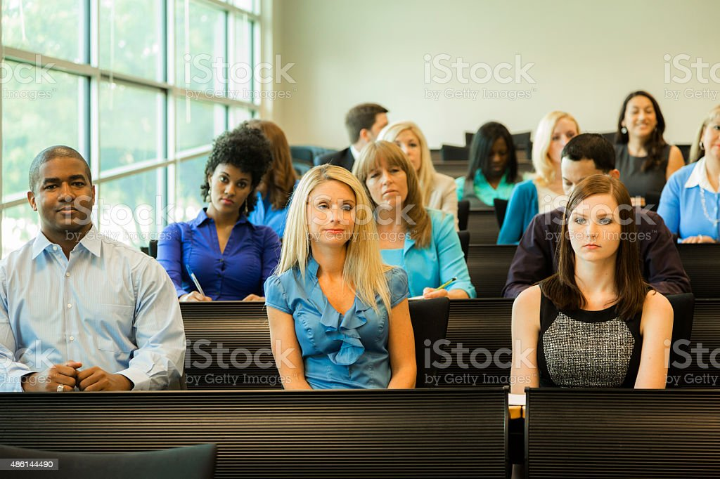 Multi-ethnic group of bored college students in classroom. stock photo
