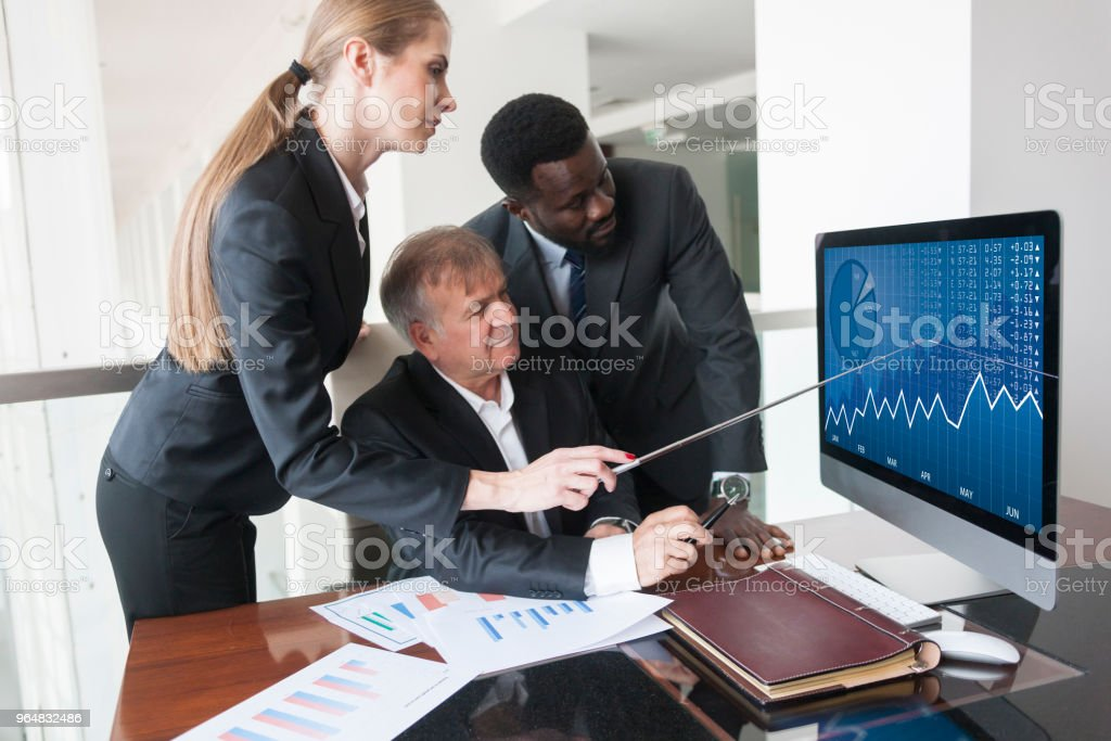 Multi-ethnic group of business executives gathered around computer screen royalty-free stock photo