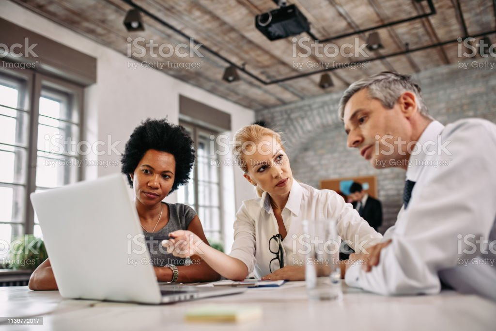 Multi-ethnic group of business people working on laptop during a meeting. royalty-free stock photo
