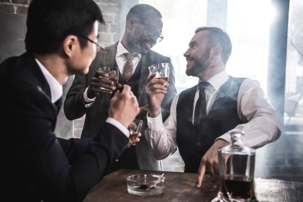 multi-etnische groep zakenlieden roken en drinken whisky binnenshuis, multiculturele business team - guy with cigar stockfoto's en -beelden