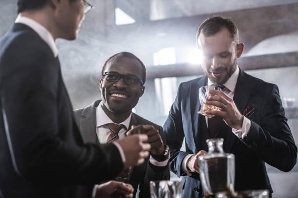 multi-etnische groep zakenlieden tijd doorbrengen samen whisky drinken en roken, multiculturele business team - guy with cigar stockfoto's en -beelden