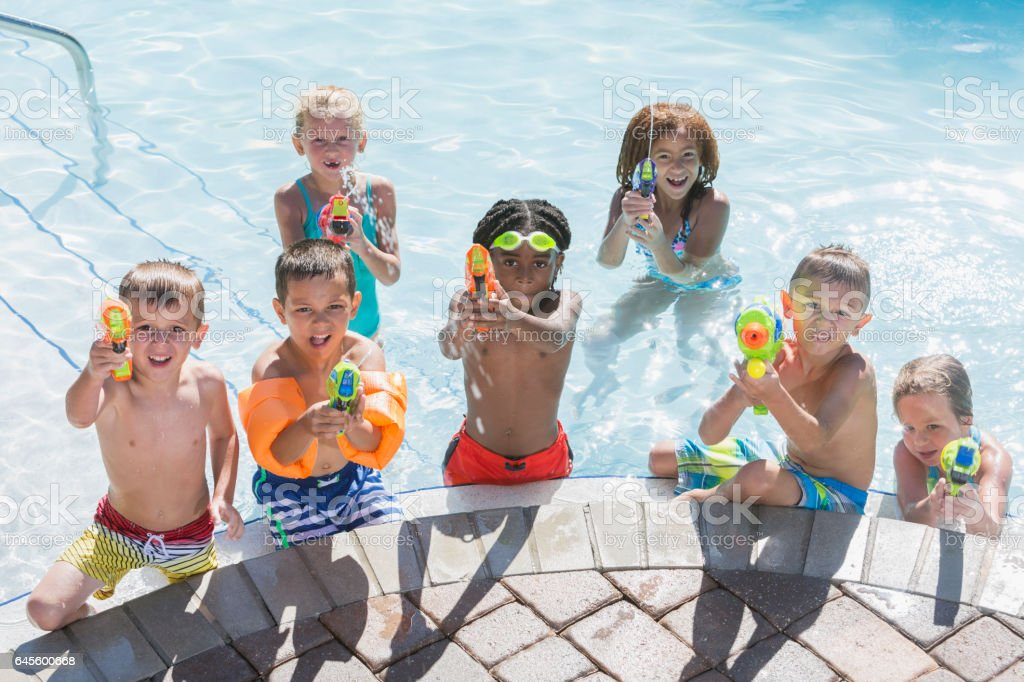 Multi-ethnic group of children in pool with squirt guns stock photo
