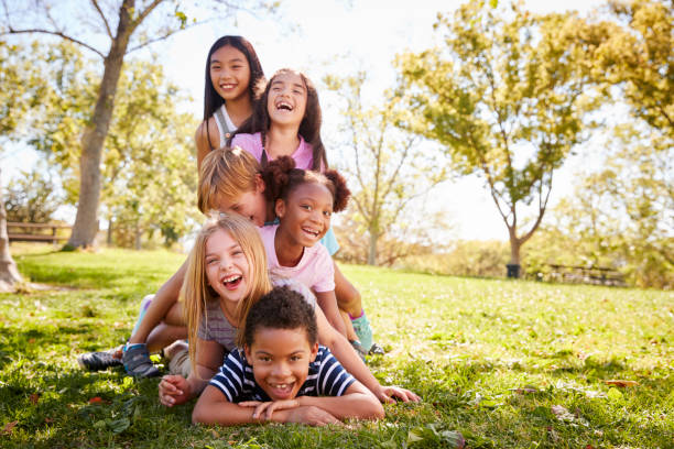 Multi-ethnic group of children lying in a pile in a park Multi-ethnic group of children lying in a pile in a park monkeybusinessimages stock pictures, royalty-free photos & images