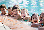 A multi-ethnic group of six children, 6 to 9 years old, having fun at a swimming pool, in the water hanging onto the side, in a row, laughing and looking at the camera.