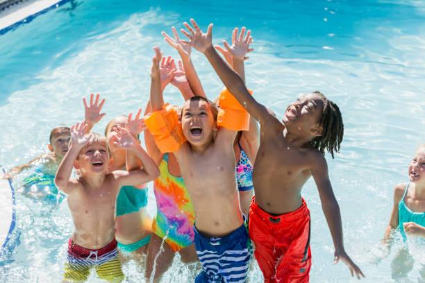 multi-ethnischen gruppe von kindern beim spielen im schwimmbad - kinderparty spiele stock-fotos und bilder