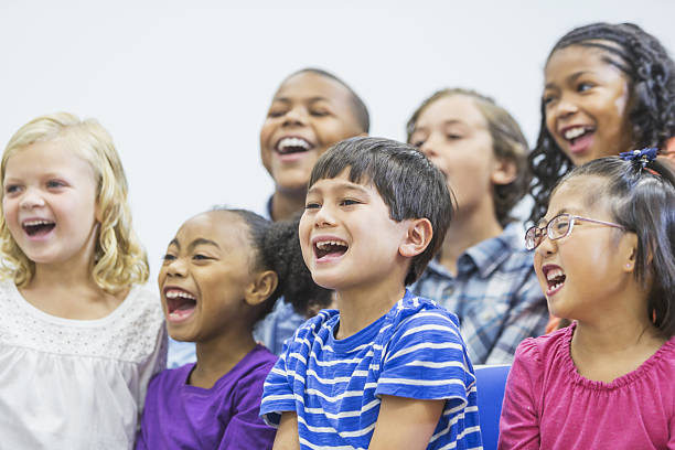 Multi-ethnic group of children sitting together shouting stock photo