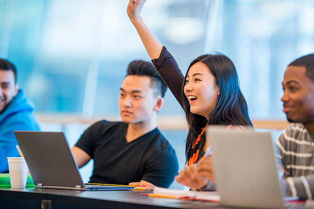 A multi-ethnic group of college students are sitting stock photo