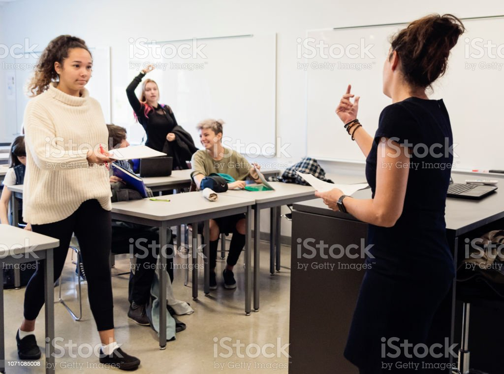 Multi-ethnic group of College students leaving classroom. stock photo