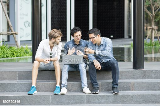 istock Multiethnic group of college students or asian freelance coworker using smartphone and laptop computer together. Lifestyle with information technology gadget, education, or social network concept 690750346