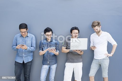istock Multiethnic group of college students or asian freelance coworker using smartphone and laptop computer together. Lifestyle with information technology gadget, education, or social network concept 690750364