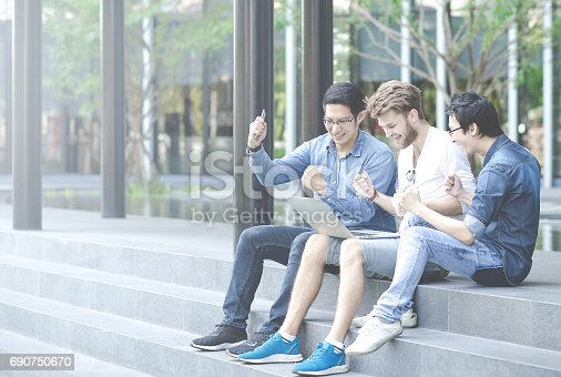istock Multiethnic group of college students or asian freelance coworker using using laptop with happy and celebrate action. Lifestyle with information technology gadget, education, or social network concept 690750670