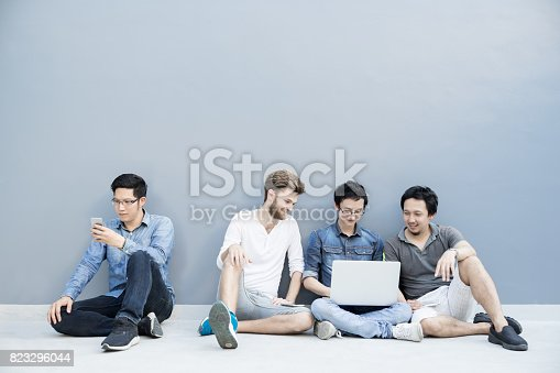 istock Multiethnic group of college students or asian freelance coworker using smartphone and laptop computer together. Lifestyle with information technology gadget, education, or social network concept 823296044