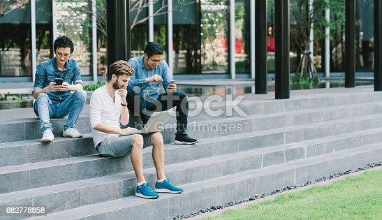 istock Multiethnic group of college students or freelance coworker using smartphone and laptop computer together. Lifestyle with infomation technology gadget, education, or social network concept 682778858