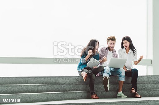 istock Multiethnic group of college students or freelance coworkers celebrate together with laptop and tablet. Creative team or business colleague at modern office. Startup, teamwork, success project concept 685128148