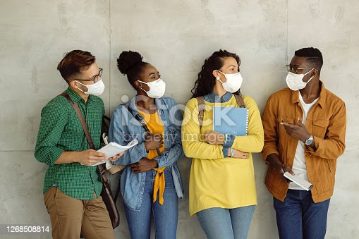 Small group of university students wearing protective face masks while talking by the wall in a hallway.
