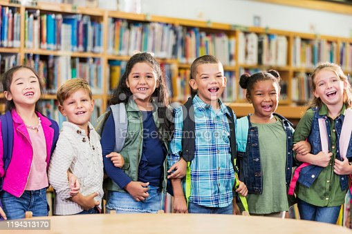 A multi-ethnic group of six children, 6 and 7 years old, standing in the elementary school library, side by side, arm in arm, smiling and laughing at the camera.