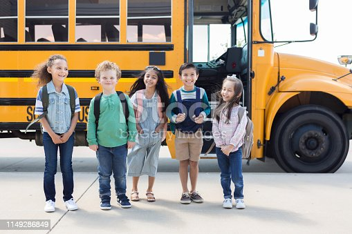 A multi-ethnic group of children poses for a first day of school photo while waiting to get on the bus.