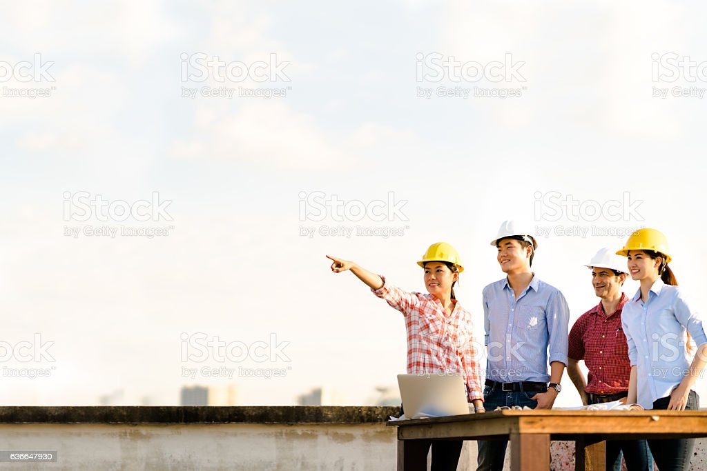 Multiethnic group of engineers at construction site, pointing at copyspace stock photo