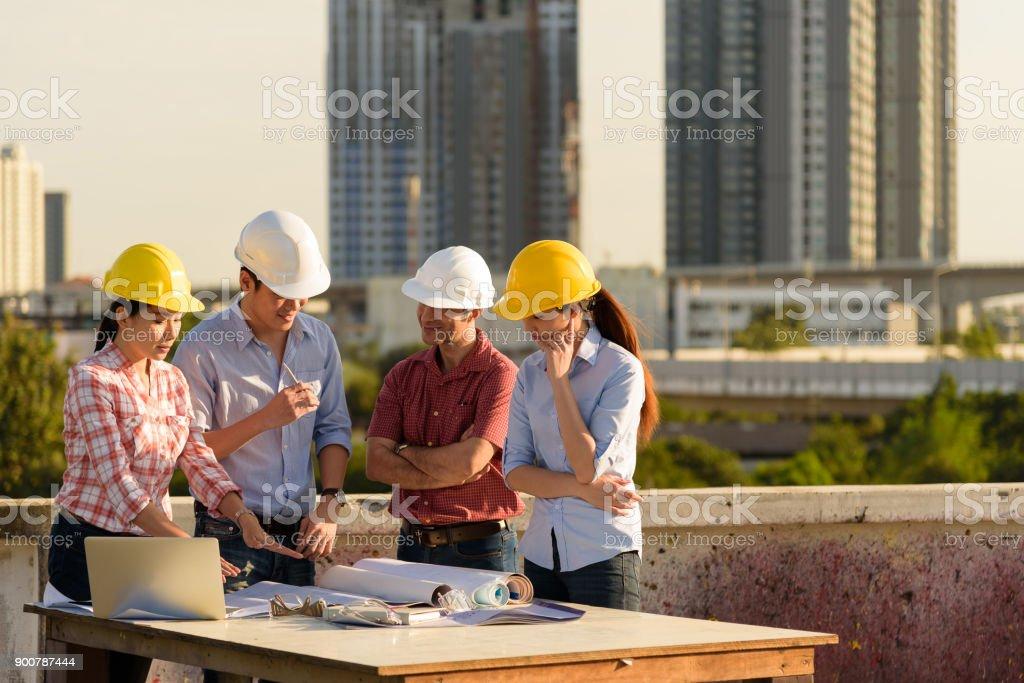 Grupo Multiétnico De Ingenieros Reunidos En La Terraza Sobre El Emplazamiento De La Obra En Tiempo De La Tarde Foto De Stock Y Más Banco De Imágenes