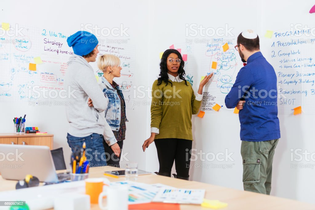 Multi-ethnic group of experts debating in teamwork in office with flipcharts stock photo