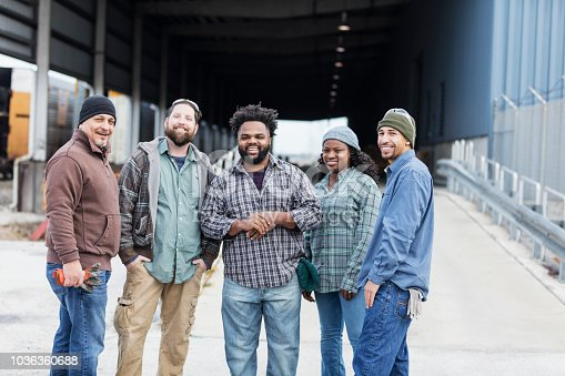 A multi-ethnic group of five manual workers standing side by side, smiling at the camera. The four men and one woman are wearing jeans, plaid shirts and knit hats. They are outdoors at a shipping port.