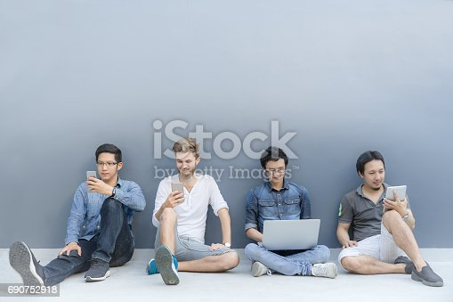 istock Multiethnic group of four asain men using smartphone, laptop computer, digital tablet together with copy space on blue wall. Lifestyle with infomation technology gadget, education, or social network concept. 690752918