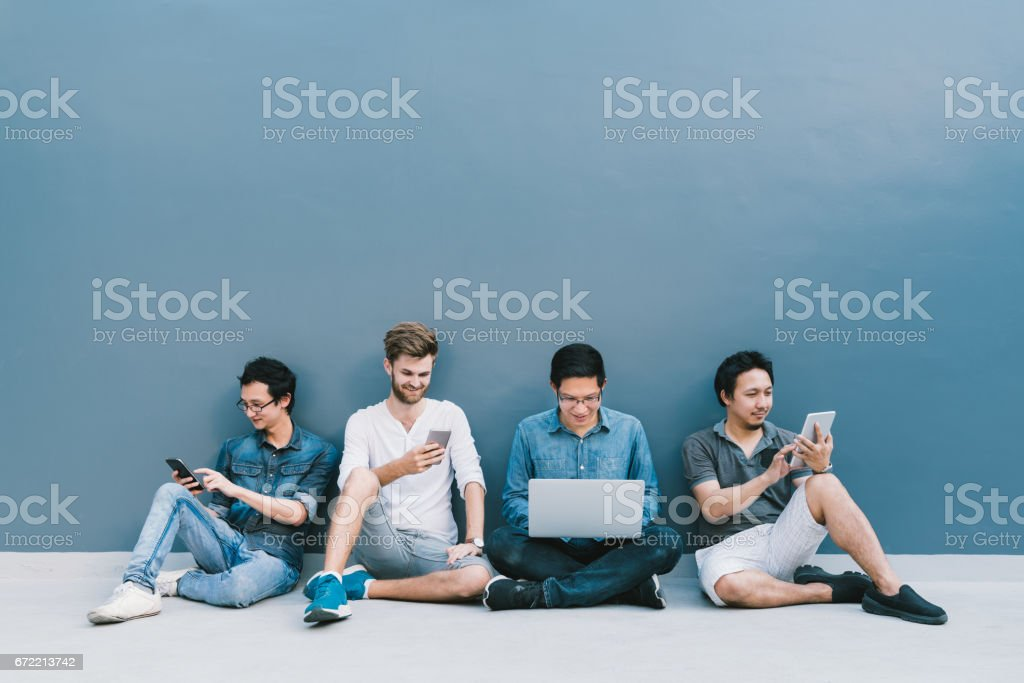Multiethnic group of four men using smartphone, laptop computer, digital tablet together with copy space on blue wall. Lifestyle with infomation technology gadget, education, or social network concept royalty-free stock photo