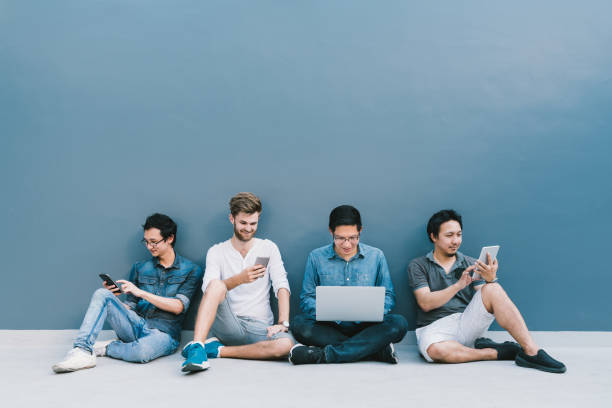 Multiethnic group of four men using smartphone, laptop computer, digital tablet together with copy space on blue wall. Lifestyle with infomation technology gadget, education, or social network concept stock photo