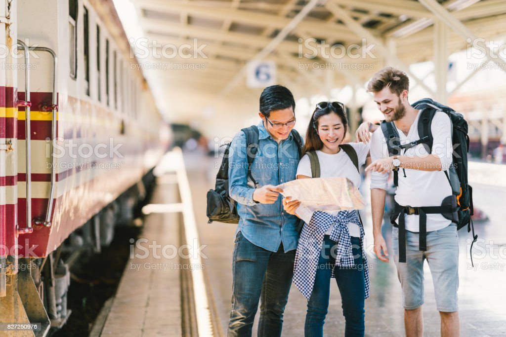Multiethnic group of friends, backpack travelers, or college students using generic local map navigation together at train station platform. Asia tourism activity or railroad trip travelling concept royalty-free stock photo
