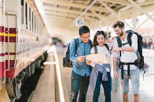 Multiethnic group of friends, backpack travelers, or college students using generic local map navigation together at train station platform. Asia tourism activity or railroad trip travelling concept