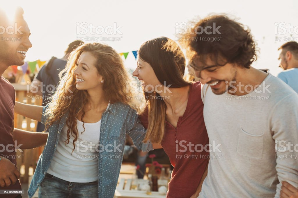 Multi-ethnic group of friends chatting on a party stock photo
