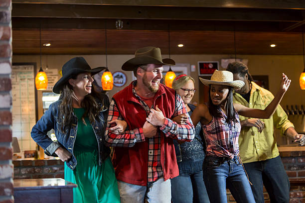 Multi-ethnic group of friends dancing in a bar A multiracial group of friends dancing in a restaurant bar, smiling and having fun.  They are wearing cowboy hats and jeans so the party has a country western theme. country and western music stock pictures, royalty-free photos & images