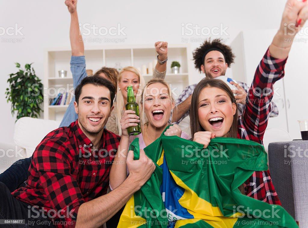 Multiétnico grupo de amigos assistir a um jogo de futebol - foto de acervo