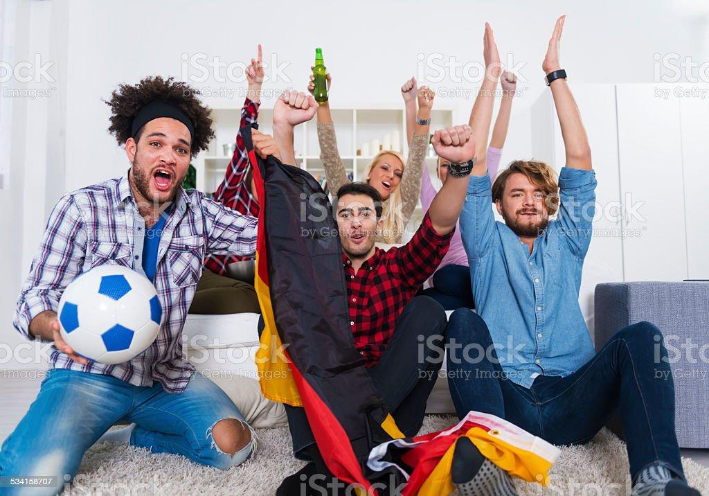 Grupo multiétnico de amigos mientras mira un juego de fútbol americano - foto de stock