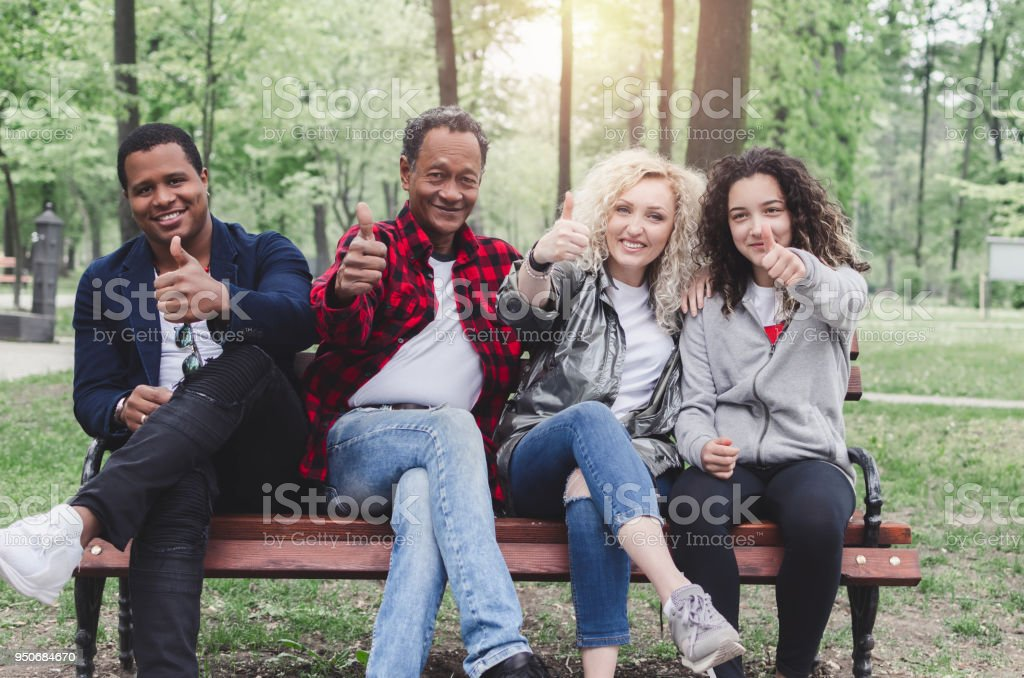Multiethnic group of happy young people sitting and showing ok gesture stock photo