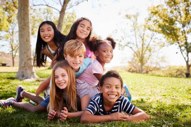 gruppo multietnico di bambini sdraiati l'uno sull'altro in un parco - bambino foto e immagini stock