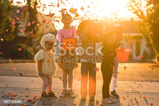 Five children of varying ages, ethnicities, and costumes go trick or treating. They include a cowboy, a duck, a fitness instructor, a gymnast, and a black cat. They are holding candy buckets in a residential neighborhood and they're throwing leaves in the air.