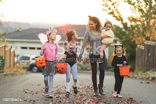 Five children of varying ages, ethnicities, and costumes go trick or treating. They include a cowboy, a duck, a fitness instructor, a gymnast, and a black cat. They are holding candy buckets in a residential neighborhood and mom, with cat ears, is holding the youngest - the duck.