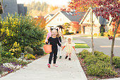 Several kids in costume go trick or treating. The focus is on a toddler-age girl dressed adorably in a black cat costume, as she runs down the sidewalk with a big smile.