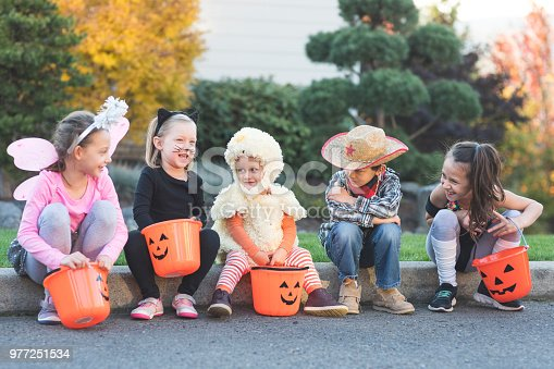 A multiethnic group of kids go trick or treating in a residential neighborhood. They're all sitting on a curb hanging out with their pumpkin candy buckets. There's a fairy, a black cat, a duck, a cowboy, and an exercise instructor.