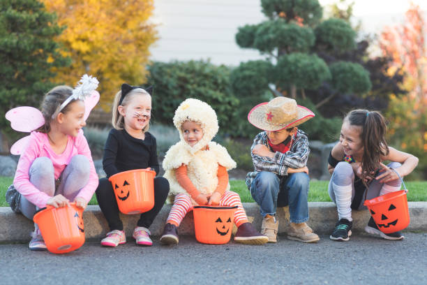 Multiethnic group of kids trick or treating A multiethnic group of kids go trick or treating in a residential neighborhood. They're all sitting on a curb hanging out with their pumpkin candy buckets. There's a fairy, a black cat, a duck, a cowboy, and an exercise instructor. costume stock pictures, royalty-free photos & images