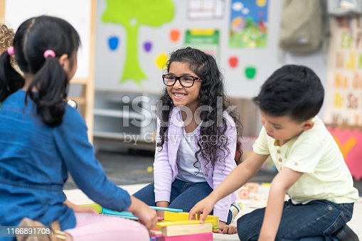 A multi-ethnic group of kindergarten students sits together on the floor in their classroom. The classmates are happily playing together. The kids are collaborating while building with wooden blocks. A Hispanic girl at the center of the frame is smiling with pride at their progress.