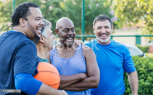 A multi-ethnic group of middle-aged and senior men on an outdoor basketball court. The Hispanic man looking at the camera is in his 40s. The African-American man standing beside him with his arms crossed is in his 50s.