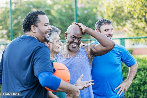 A multi-ethnic group of middle-aged and senior men on an outdoor basketball court. The African-American man looking at the camera with his hand on his head is in his 50s.