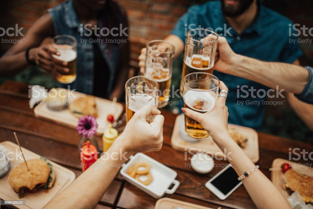 Multi-ethnic group of people celebrating social gathering at the pub stock photo