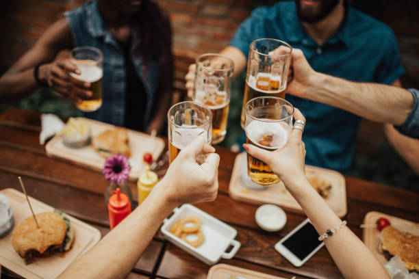 Multi-ethnic group of people celebrating social gathering at the pub stock photo