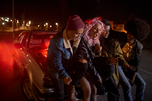 Multiethnic group of people having fun leaning on car at night stock photo